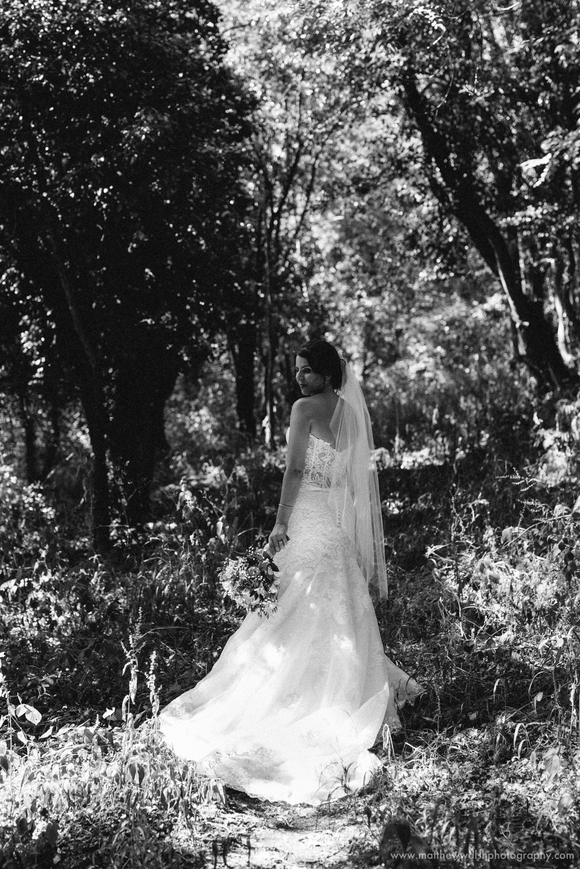 The back of the brides dress as she is framed by a natural backdrop all in wonderful black and white photography