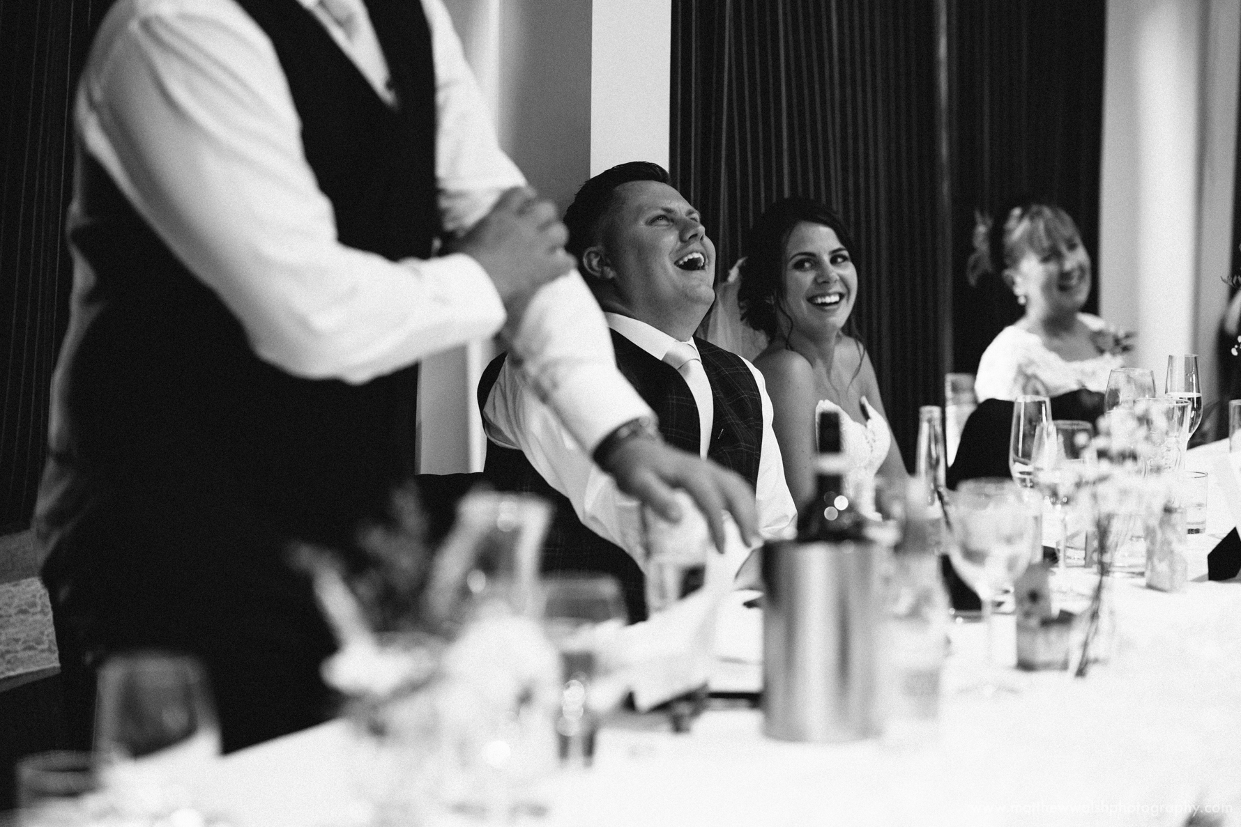 The groom laughing at the best man speech