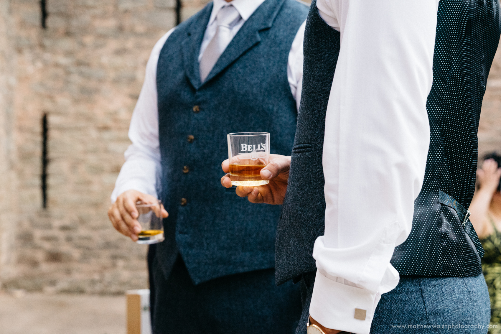 The groom calming his nerves a little more with a glass of whisky