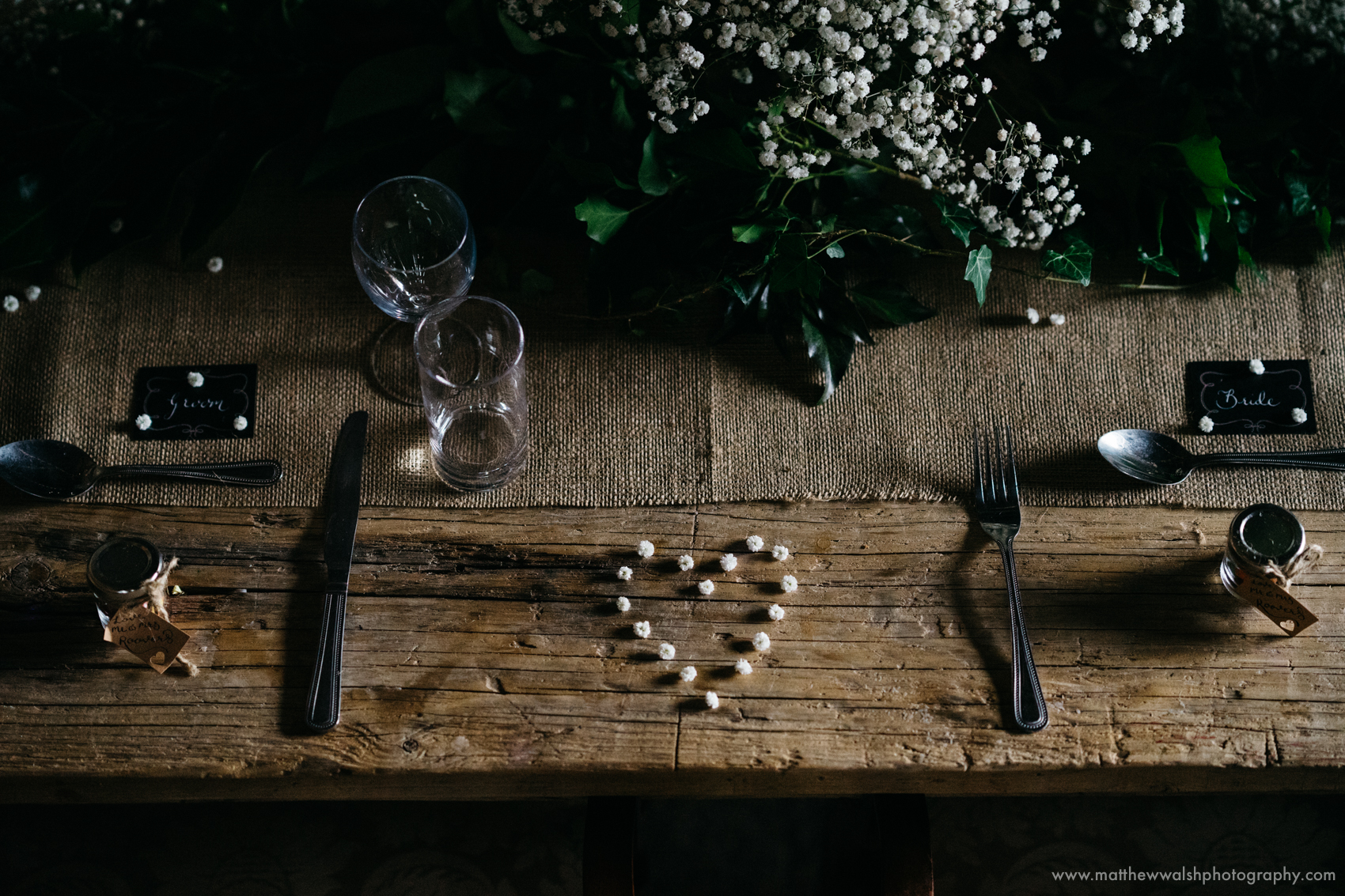 A love heart sits between the bride and grooms table settings