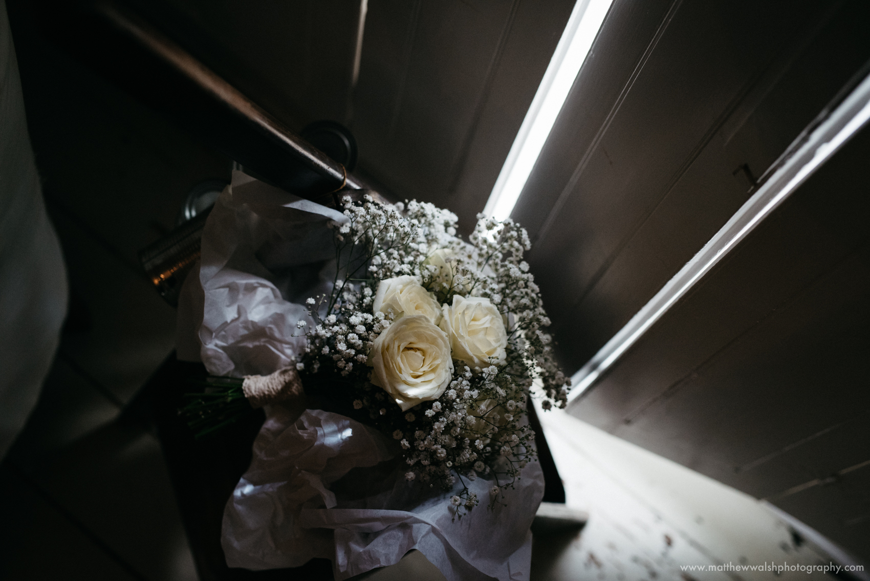 The brides bouquet also lit by a slither of light coming in through the french doors in the drawing room
