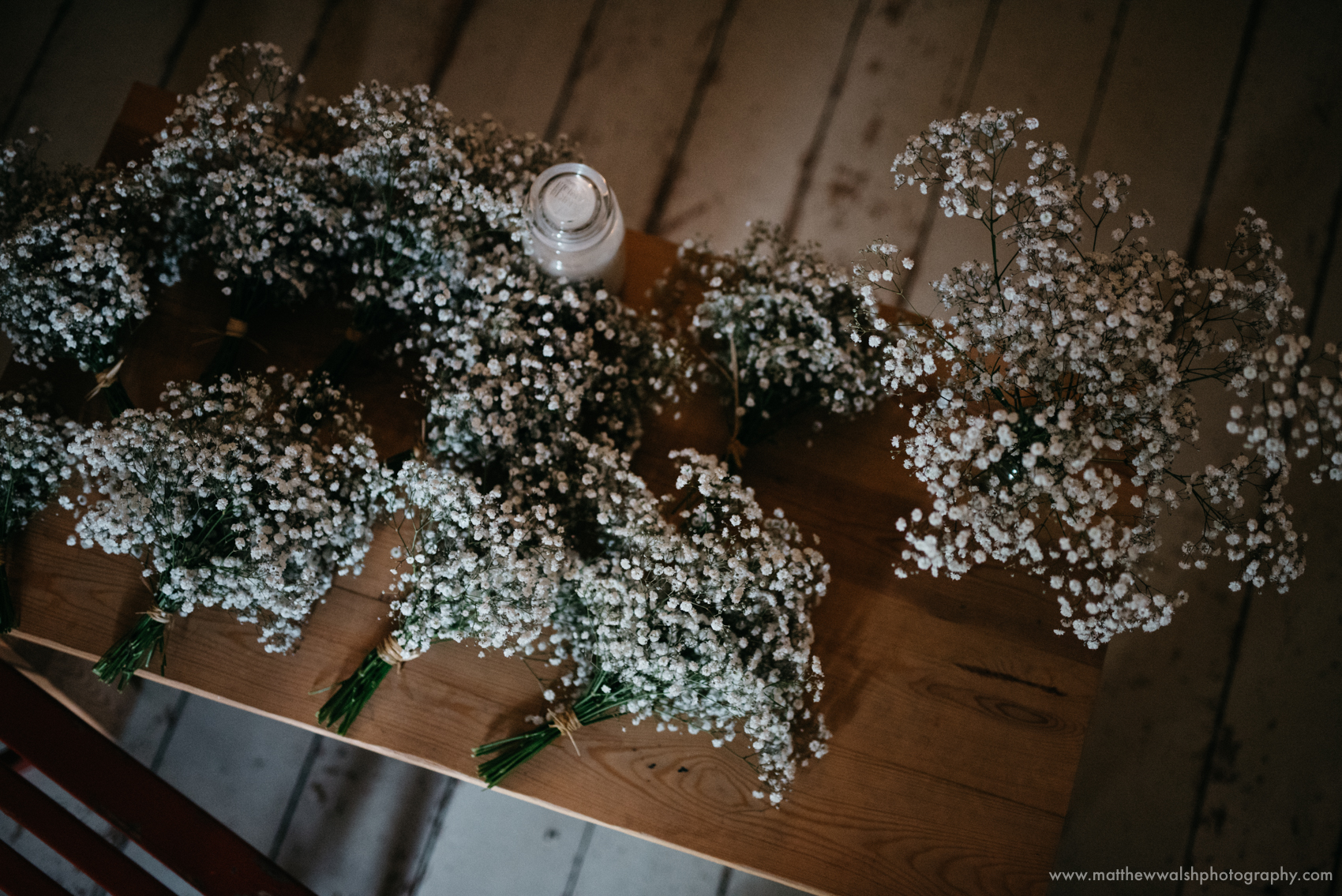 The bridesmaids flowers on a table lit by a slither of light coming through the french doors