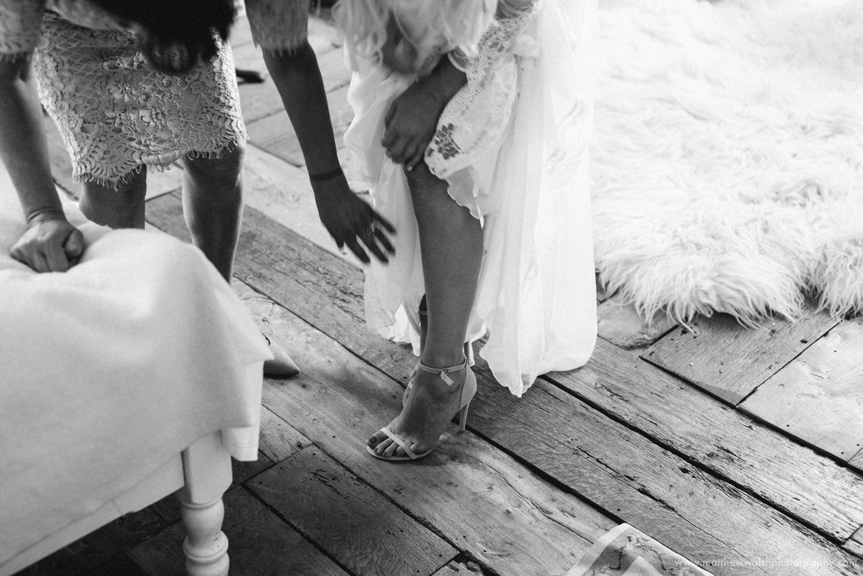 A black and white image of the bride putting her wedding shoes on