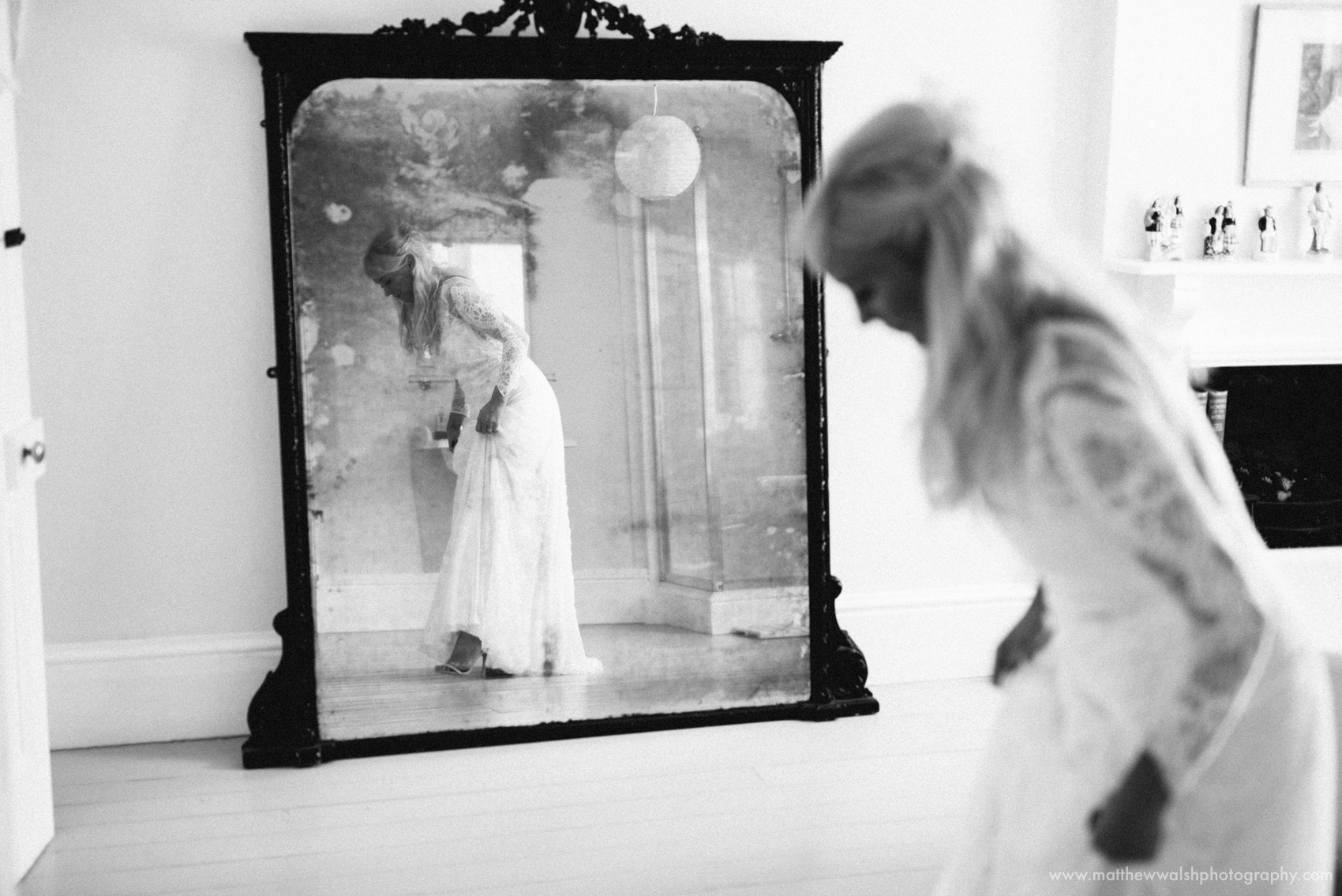The bride checks her dress in the mirror in the bridal suite at Lyde Court wedding venue