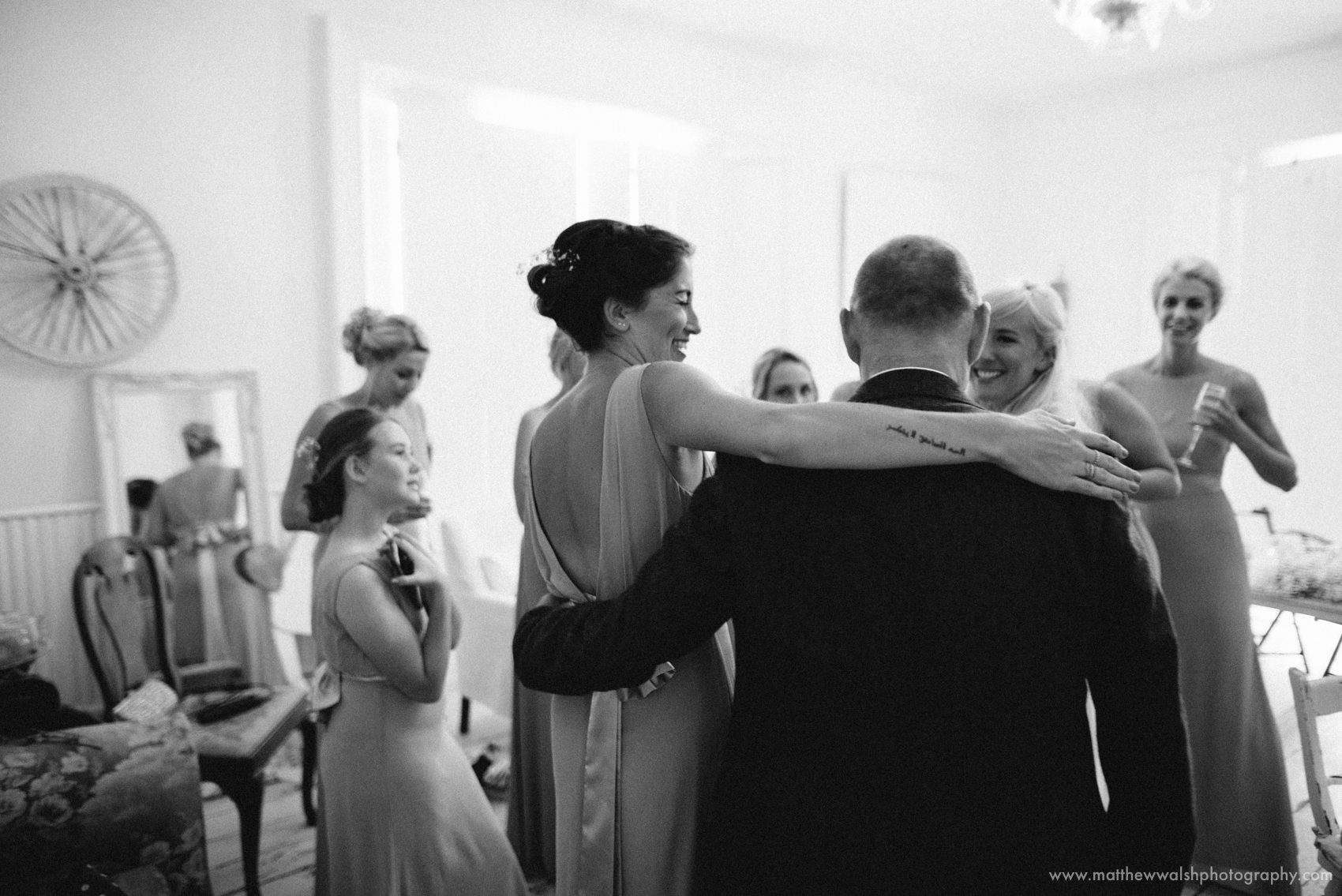 Father of the bride is welcomed into the room by the bride and bridesmaids