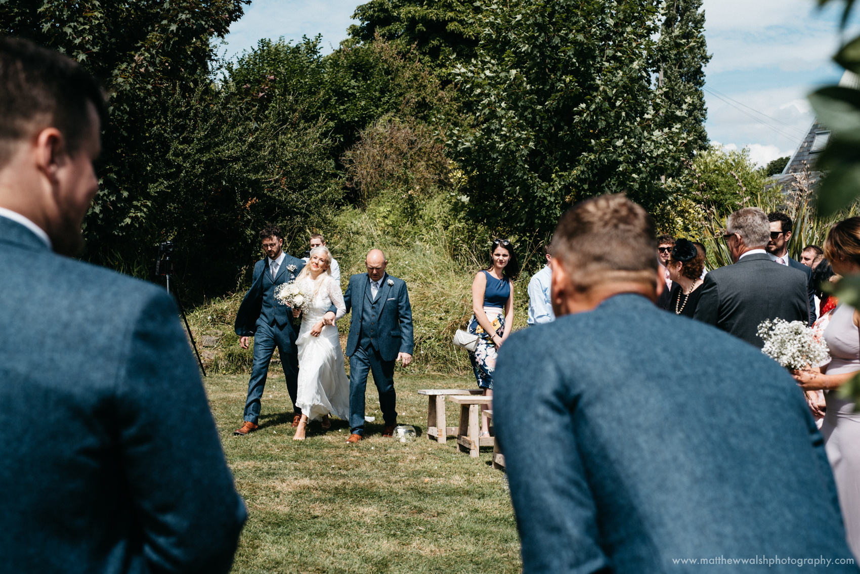 The groom is feeling very lucky and emotional as he first sees is bride walking down the isle