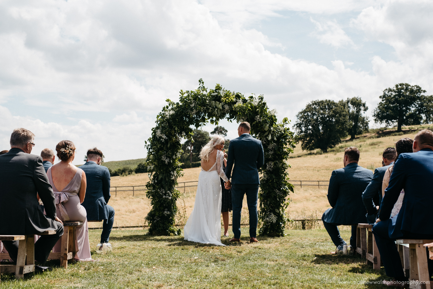 Making their vows under a floral arch that they have made themselves