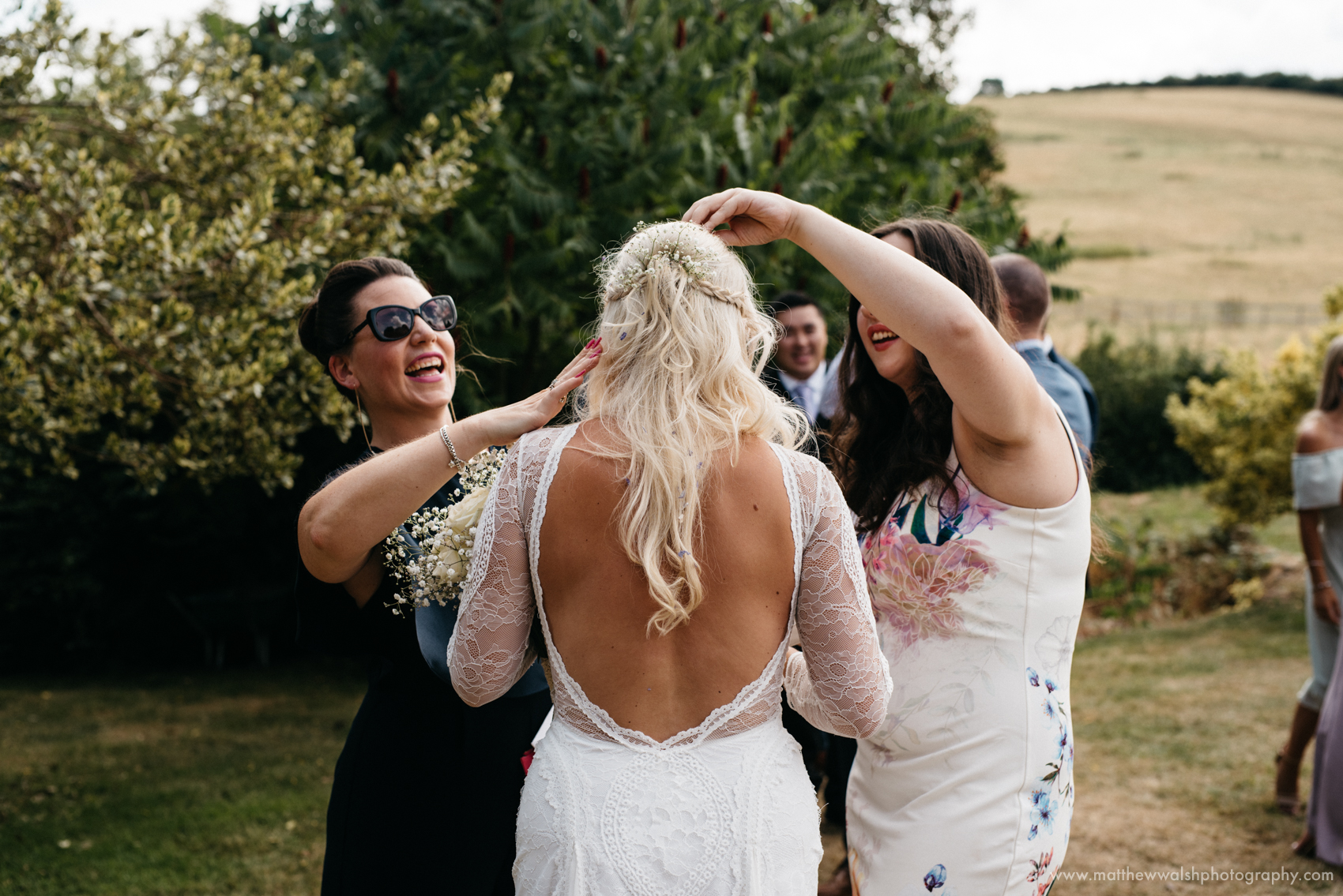 Friends of the bride help remove confetti from her hair