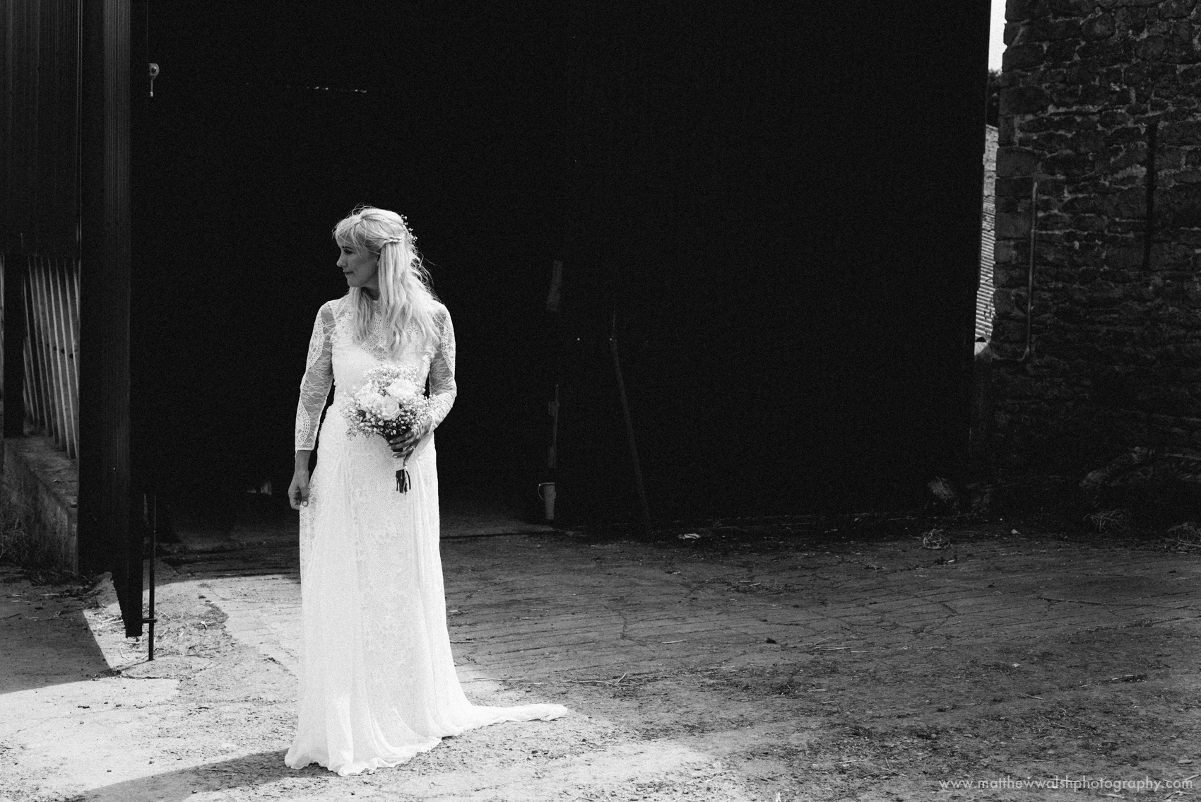 The bride looking elegant and sophisticated in her lace wedding dress, captured in black and white to make the dress really stand out