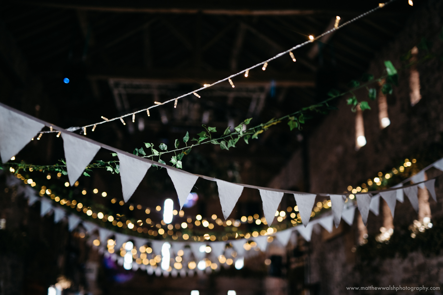 Fairy lights and bunting in the larger barn at the wedding venue