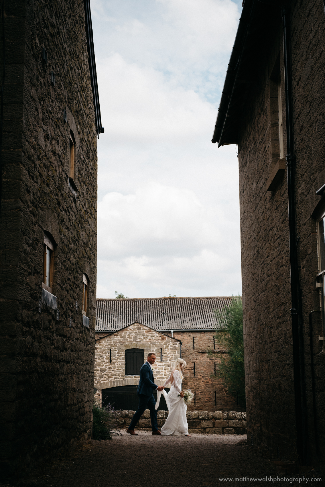 The bride and groom walking in the light, using the buildings and shadows to frame them