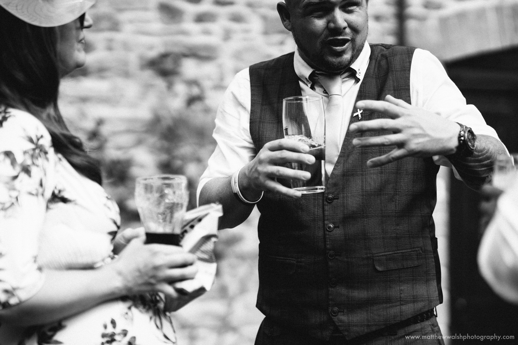 A guest getting quite animated as he tells a story to another wedding guest