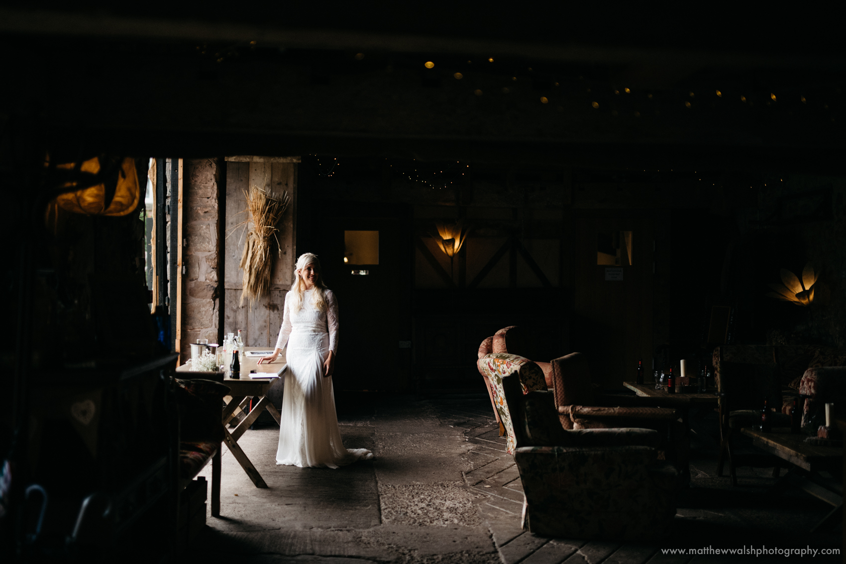An observed moment of the bride standing by the barn entrance soaked in natural light in a perfectly exposed photograph
