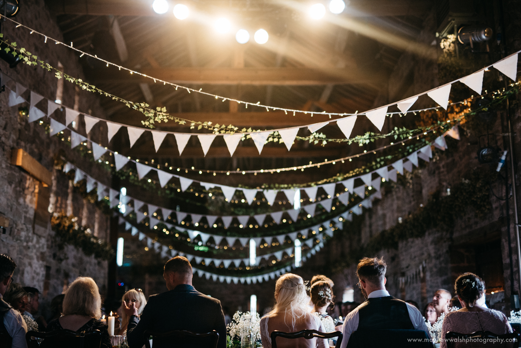All seated in the main barn, lit by the fairy lights and spot lighting above