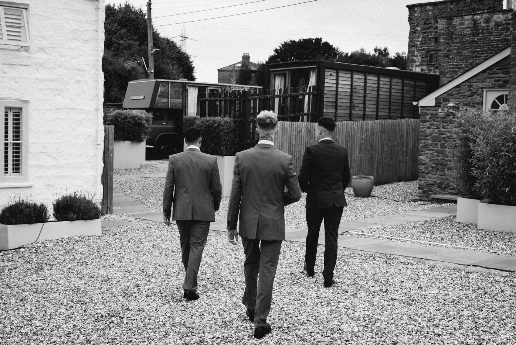 The Groom and his groomsmen walk around the grounds to look at the guest accommodation.