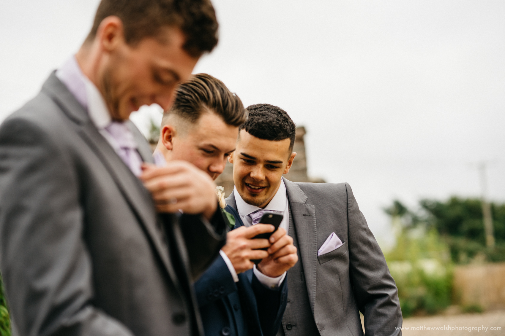 A photograph taken of the Grooms party looking at a mobile phone