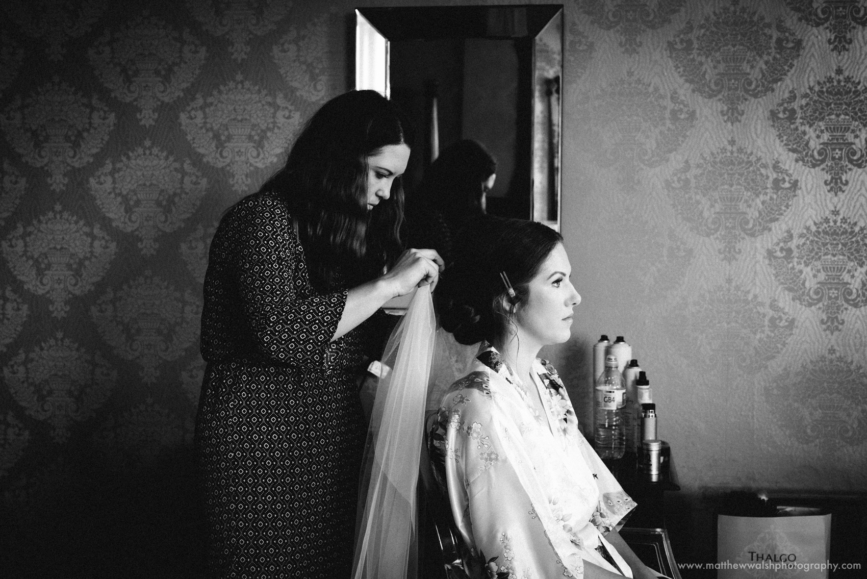 A Documentary style picture of the bride having her veil put on by the hair dresser