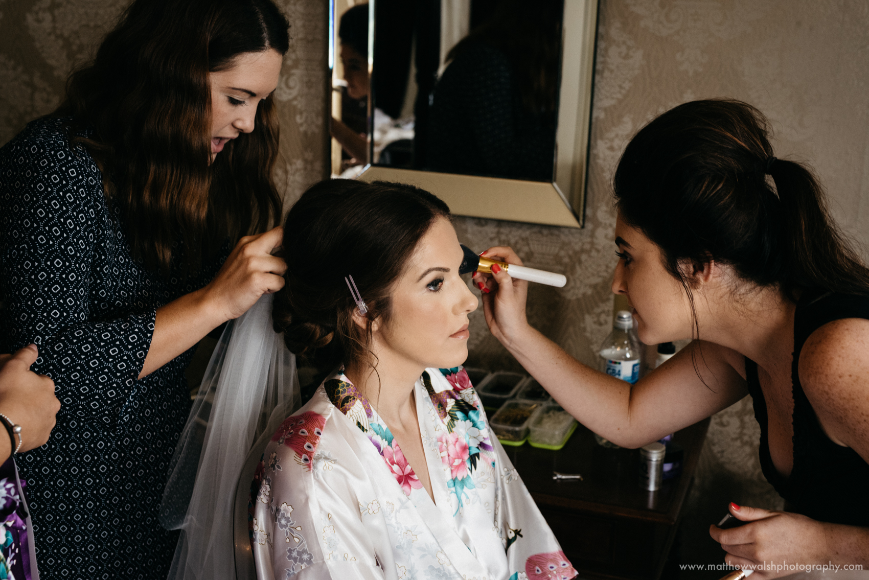 The bride has the final touches made to her makeup by the makeup artist