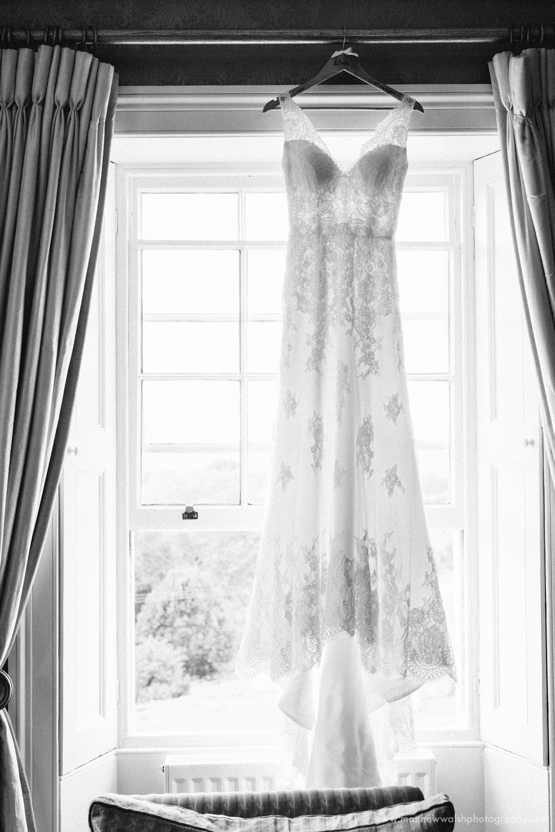 The beautiful and elegant wedding dress hanging up un the window