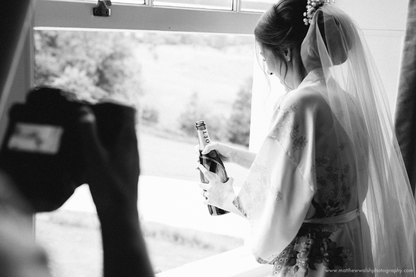 The bride opens a bottle of Champagne to be traditionally shared with her bridesmaids