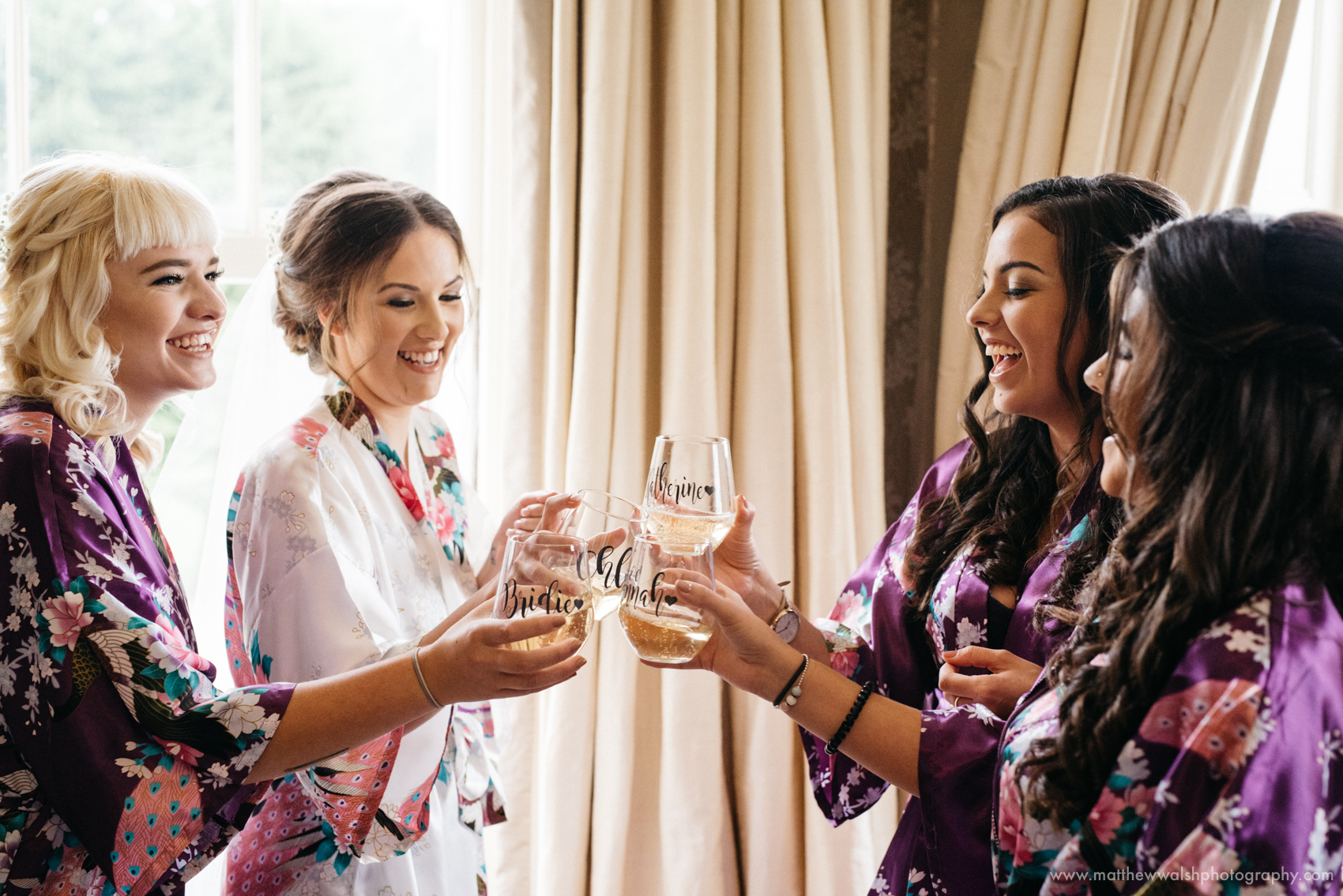 The bridesmaids share a fun cute moment as they toast the bride