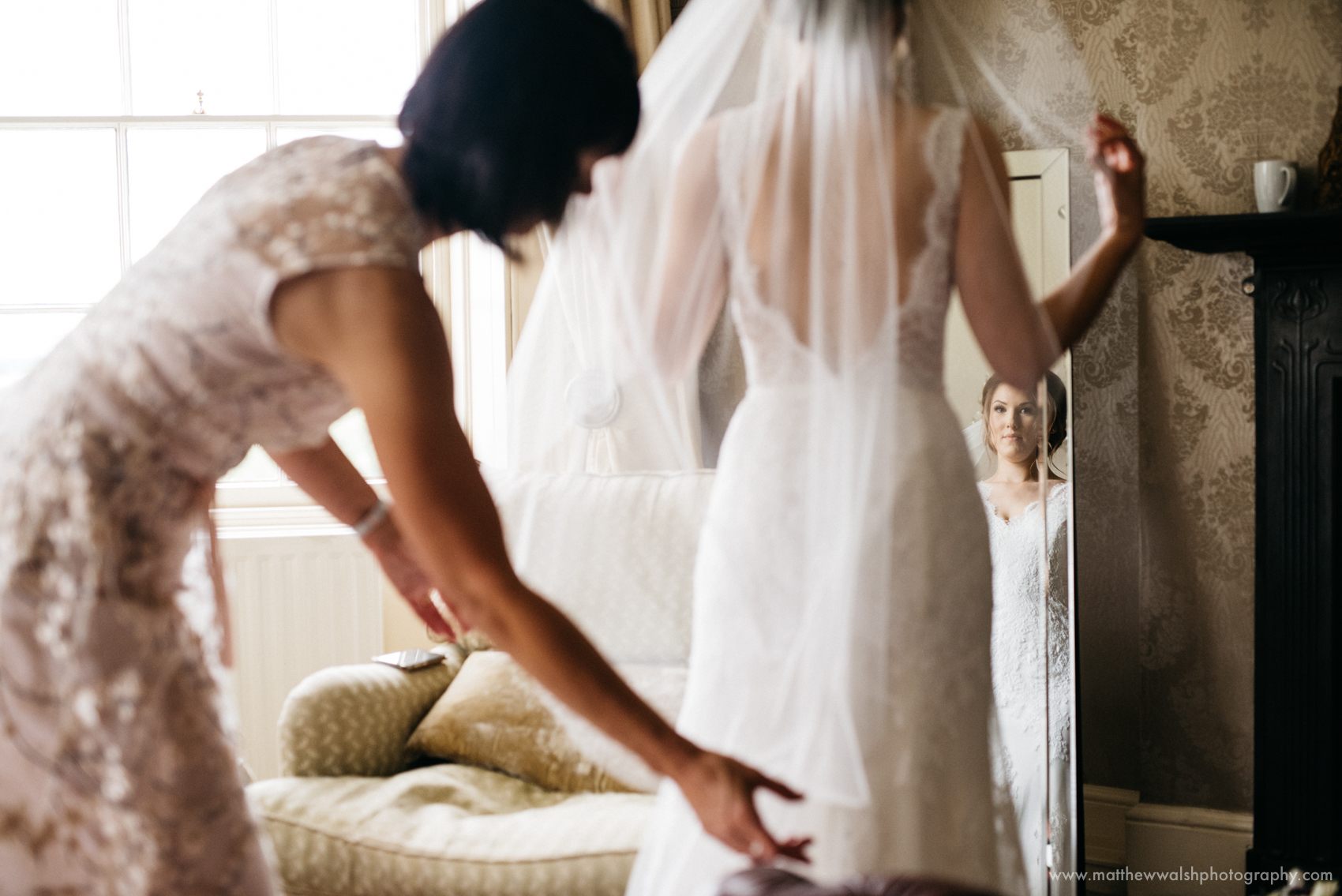A Reportage moment capturing the mother of the bride putting her dress on