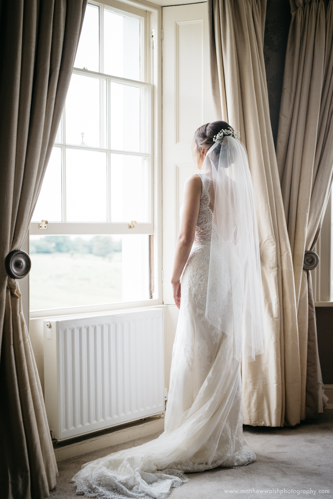 The bride looking radiant as she looks out of the window wearing her wedding dress