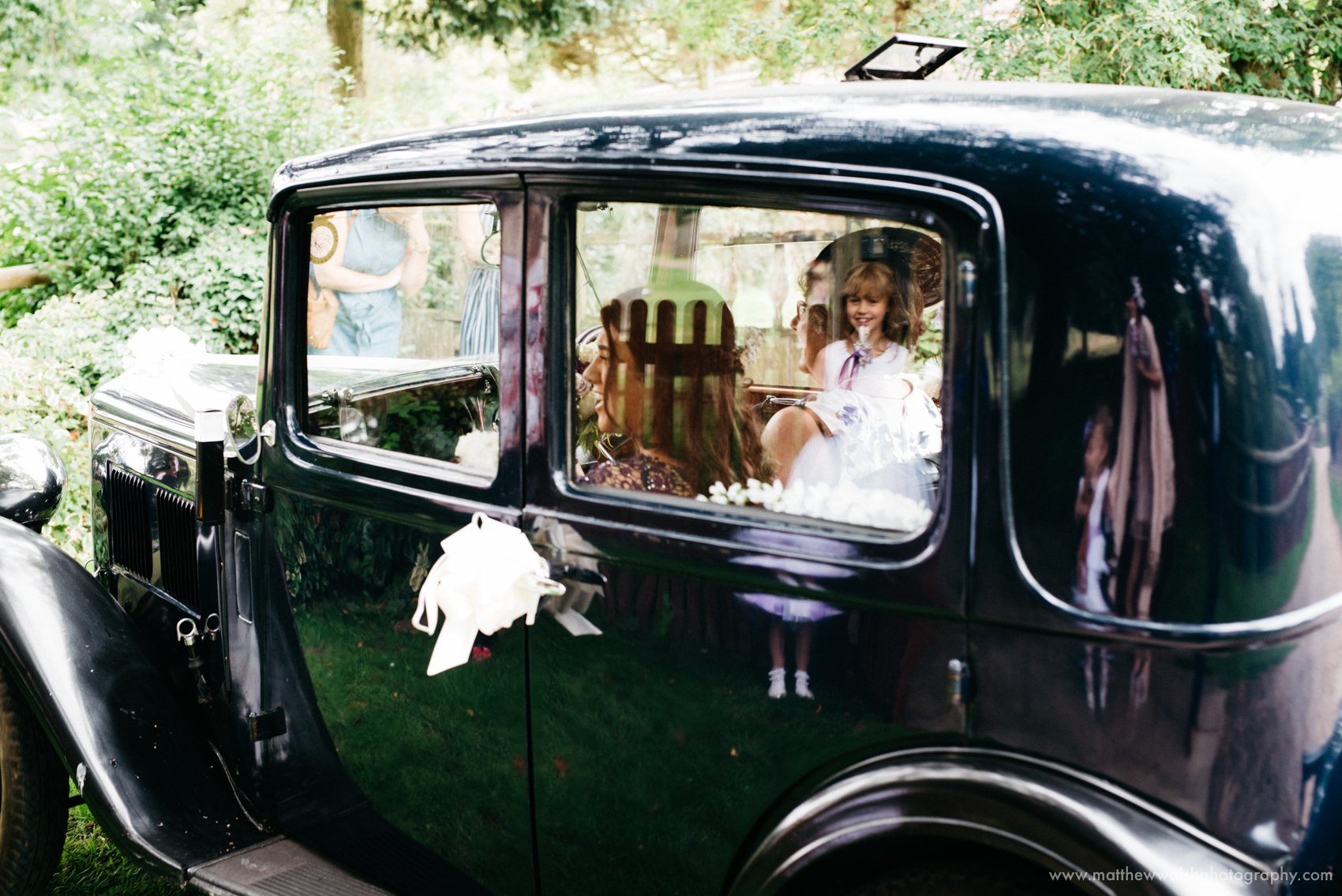 The bridesmaids arrive in an old wedding car