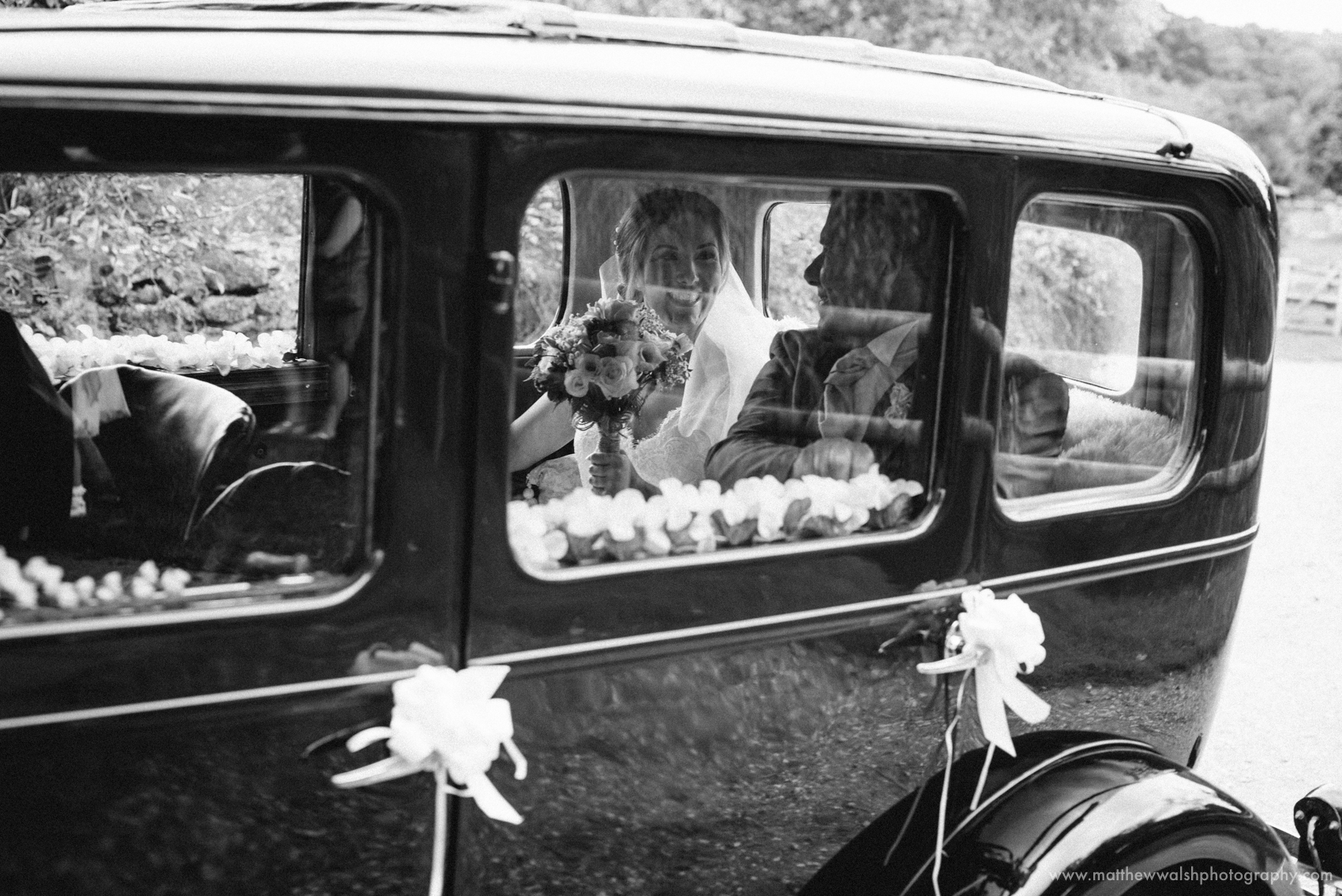 The bride with he father arrive at the ceremony in her wedding car