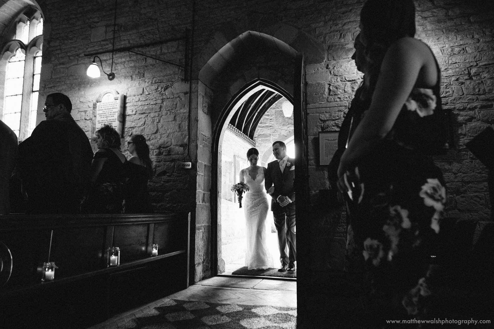 The bride being led through the Church door by her father, a lovely glowing back lit image