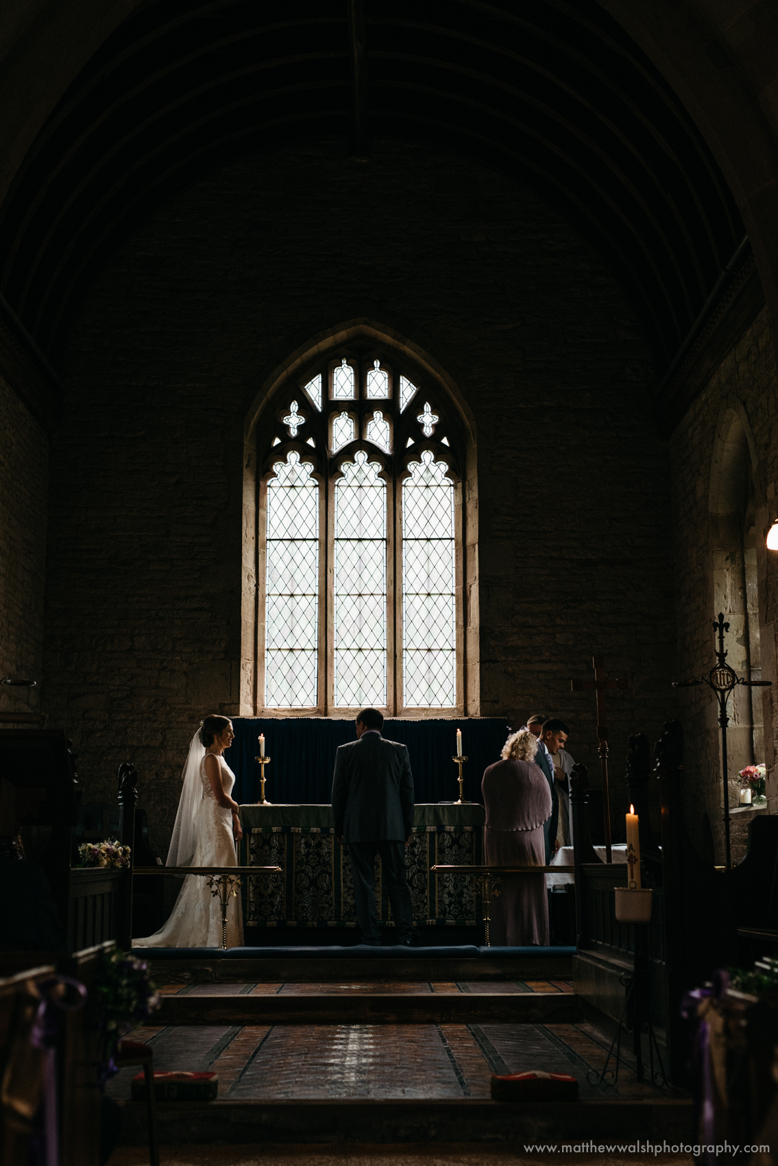 A wonderfully framed photograph of the dark church but a bright window creating a perfect glow around the bride and her dress