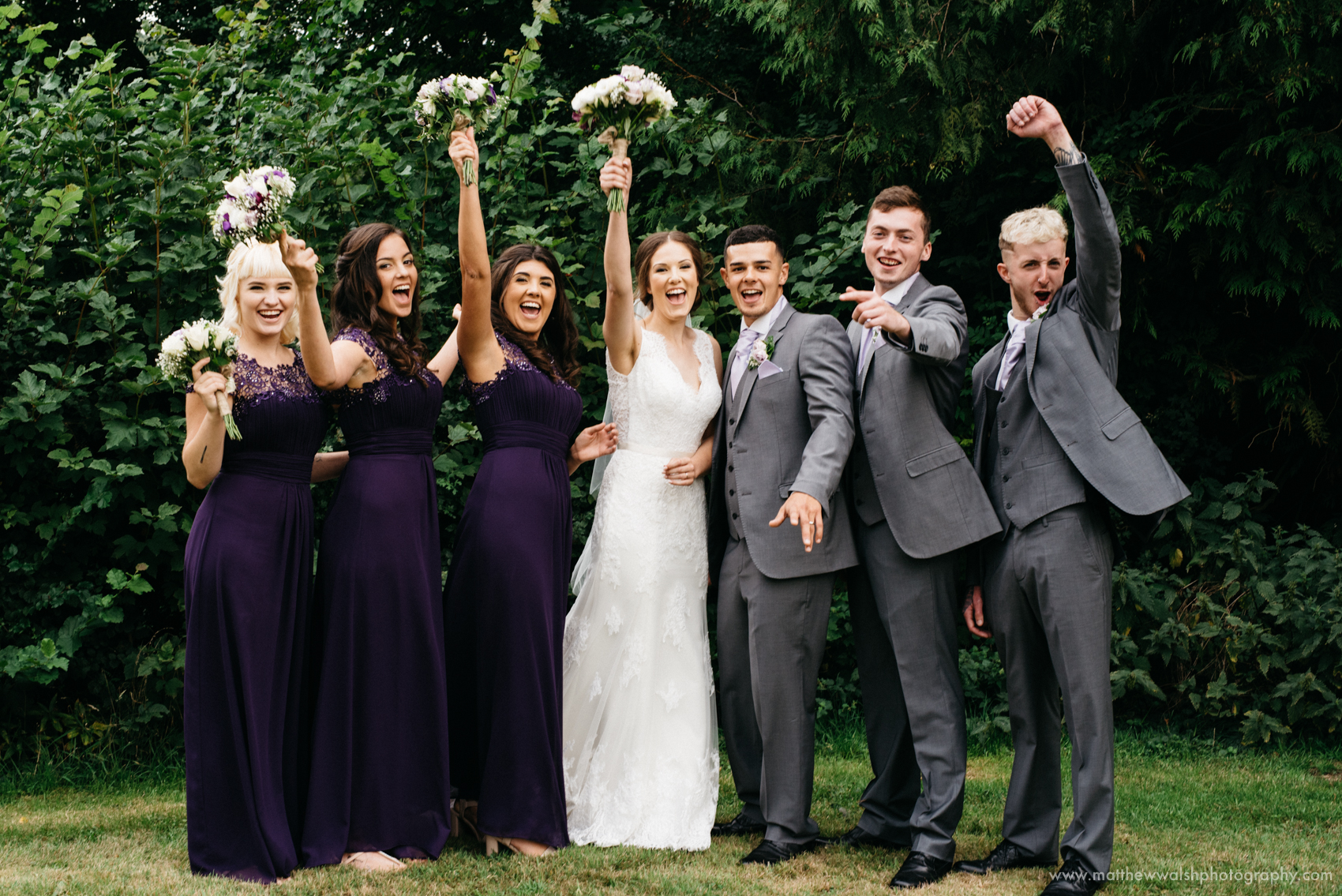 The bridesmaids and groomsmen share a more relaxed photograph together as they celebrate the happy couple