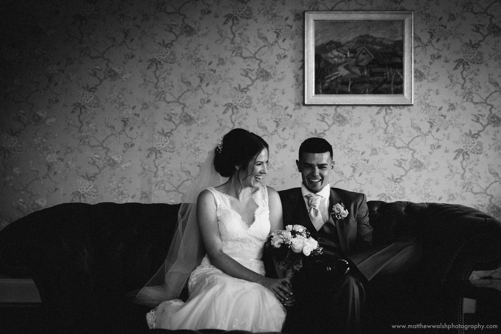 The bride and groom sat together on a couch in the games room of the venue, the natural window light creating a wonderful atmosphere