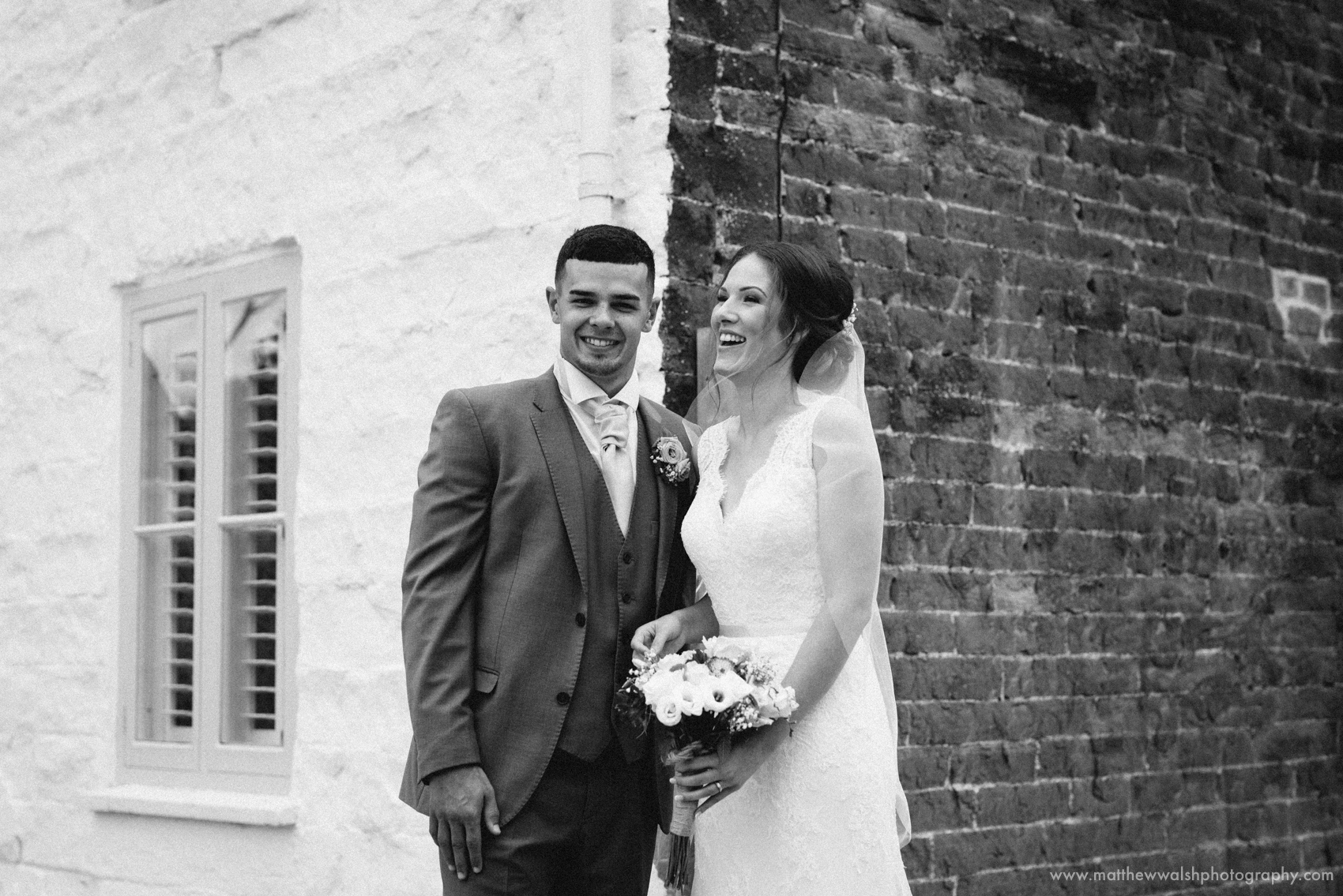 The super happy couple against the contrasting walls