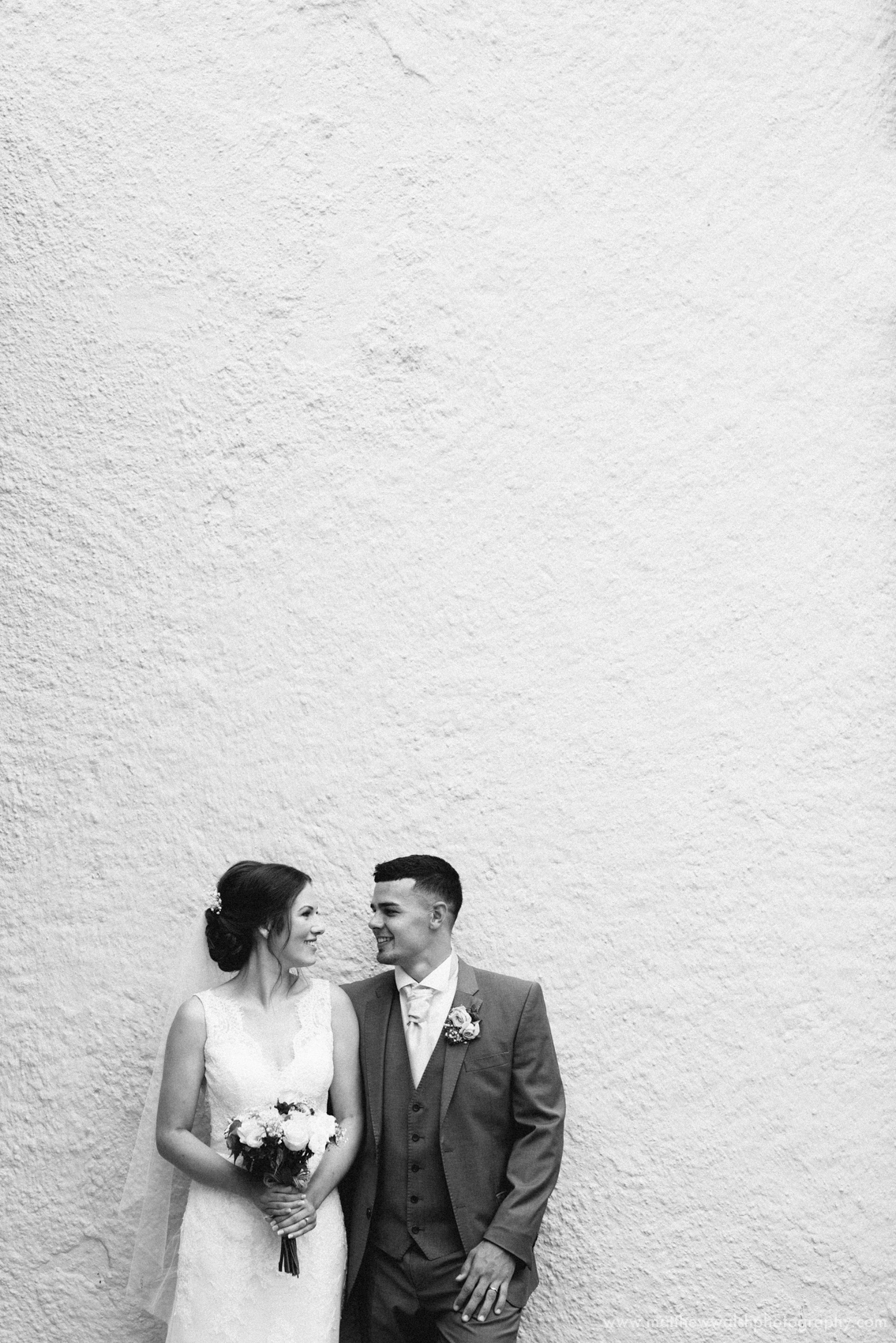 A photographic portrait of the married couple against a neutral wall with negative space