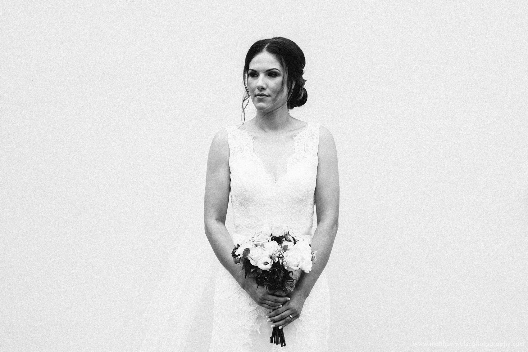 The beautiful bride standing against a white wall