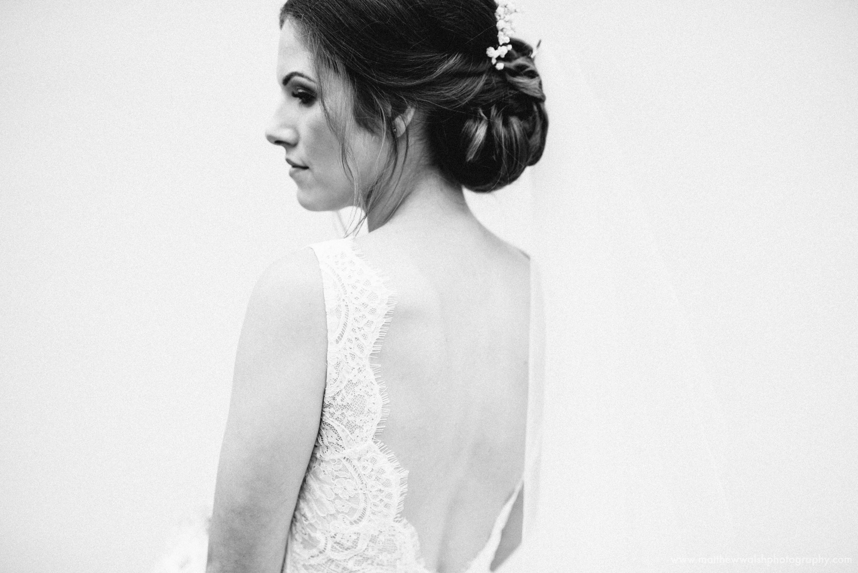 A detail of the back of the brides dress as she looks over her shoulder