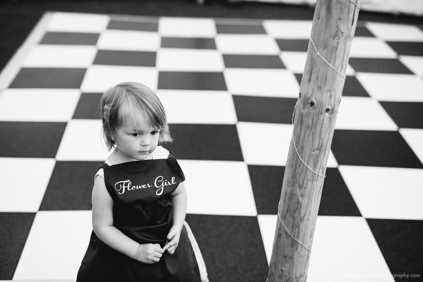 The little flower girl standing against the checked pattern of the dance floor