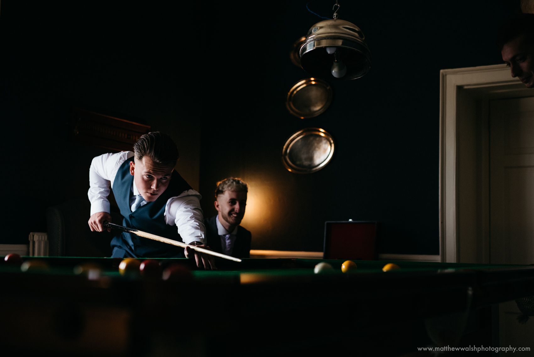 One of the groomsmen playing pool in the pool room