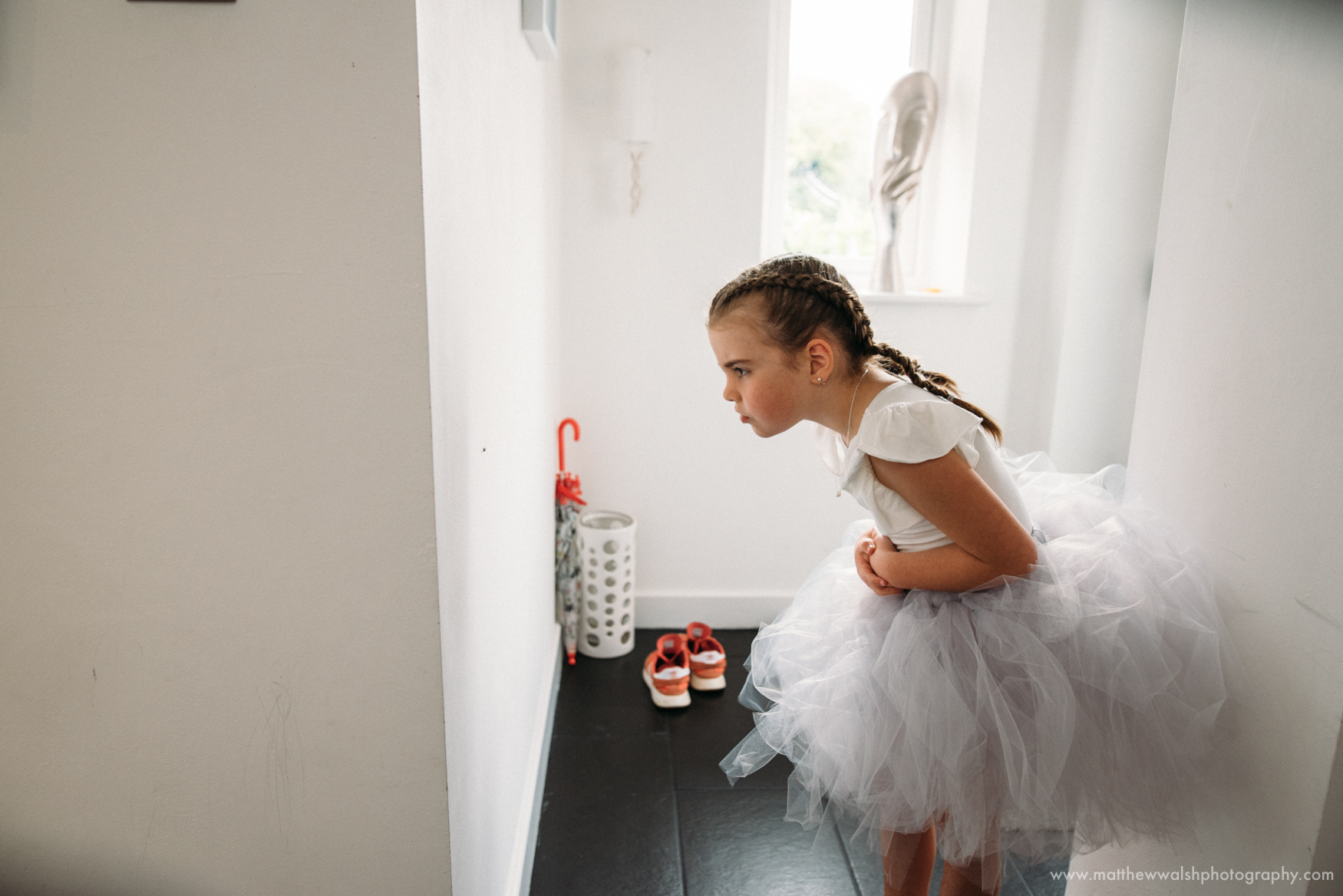 One of the flower girls inspects a spider on the wall with great interest