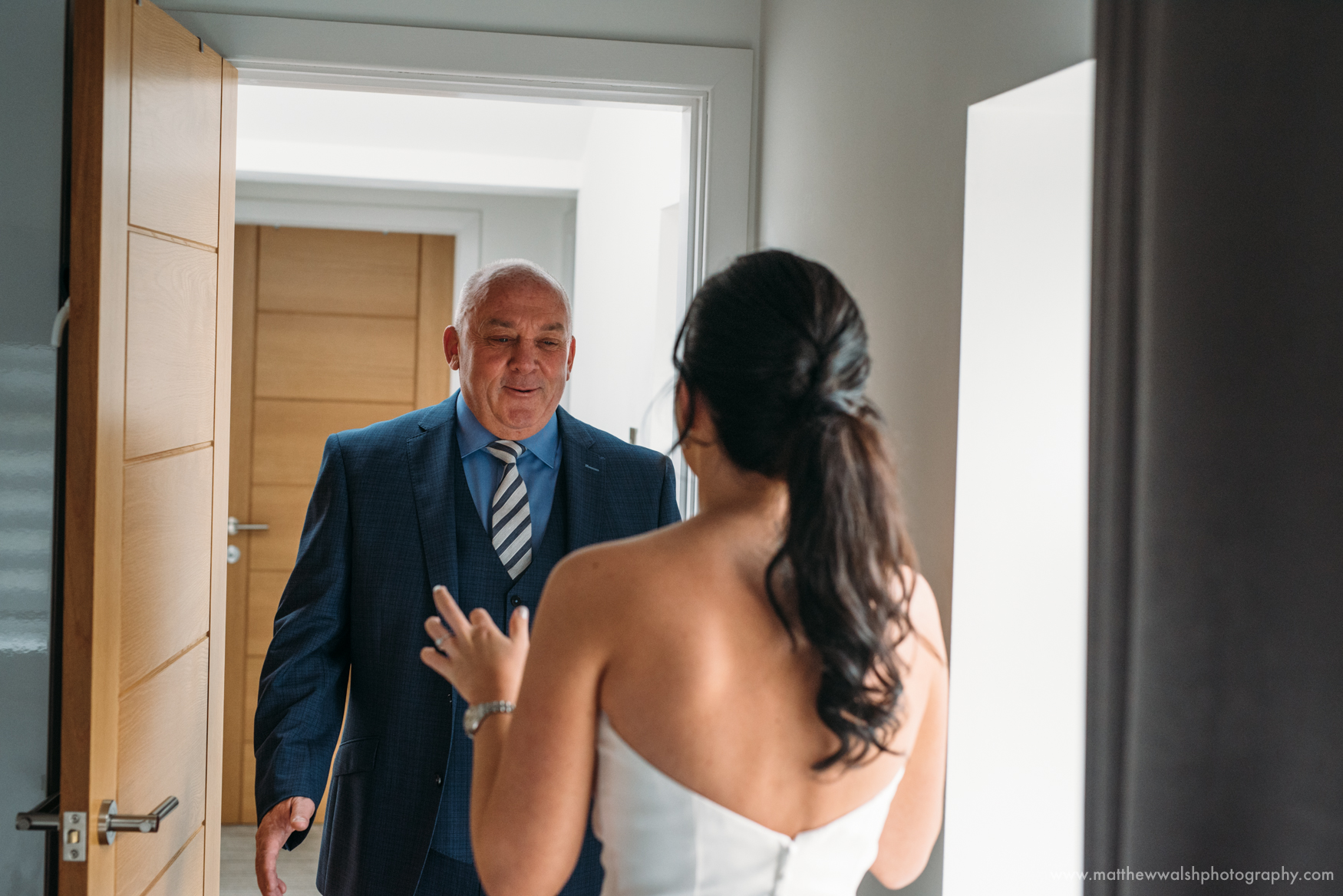 The moment captured as the father of the bride sees his daughter in her wedding dress for the first time