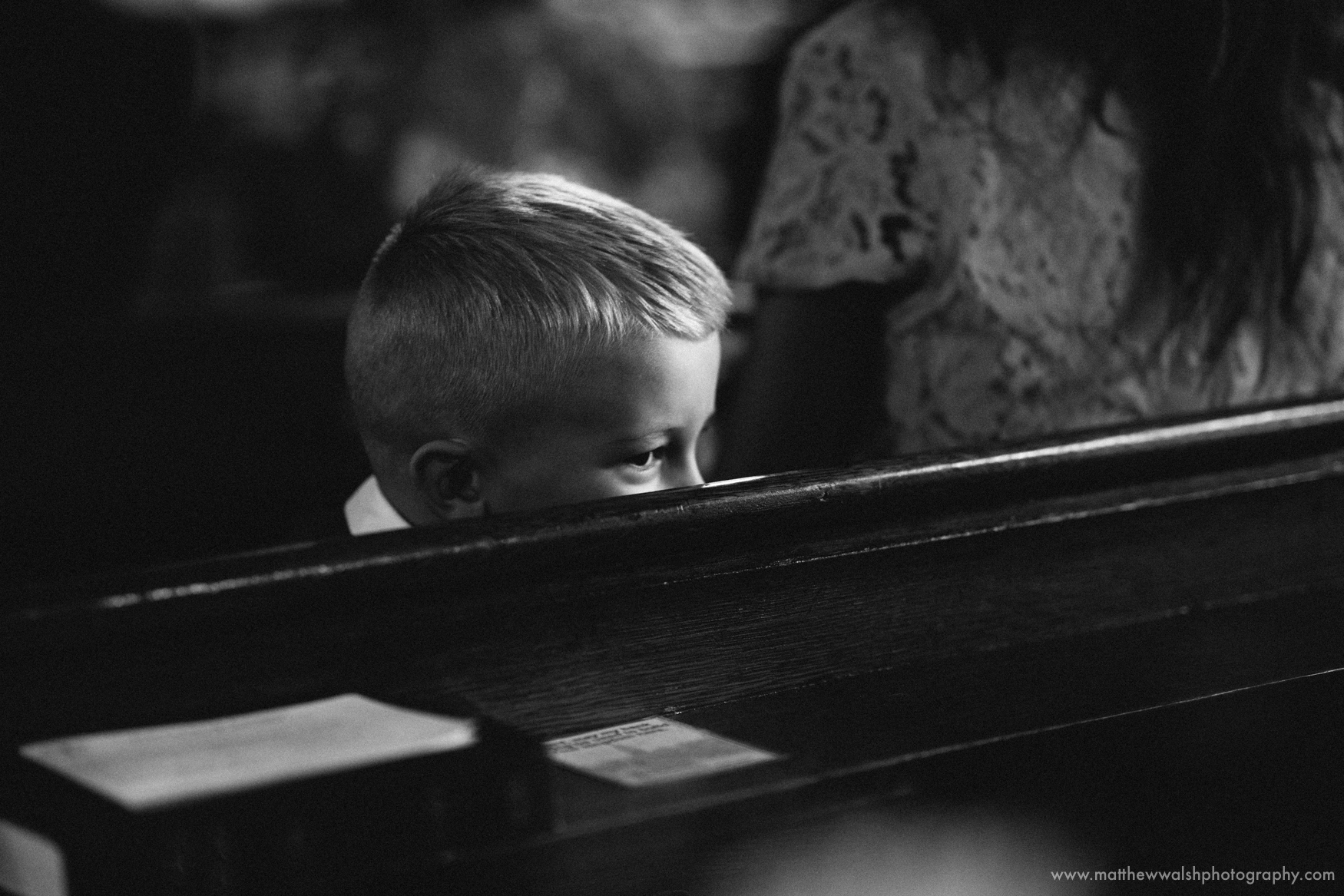 A little boy peeps over a church pew