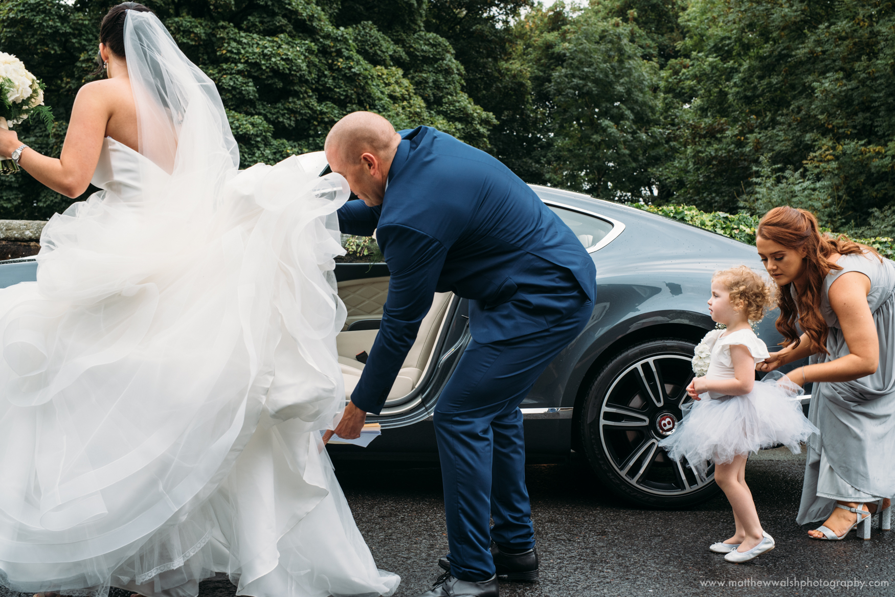 One of the ushers helps the bride to get out of the wedding car