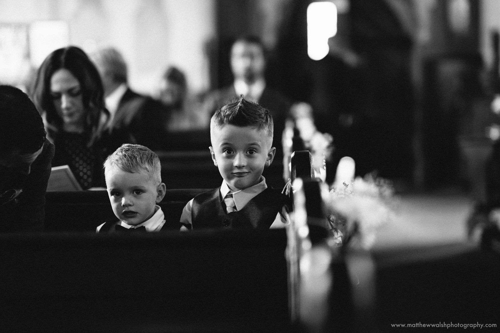 A photojournalistic image of two boys watching the bride and groom marry