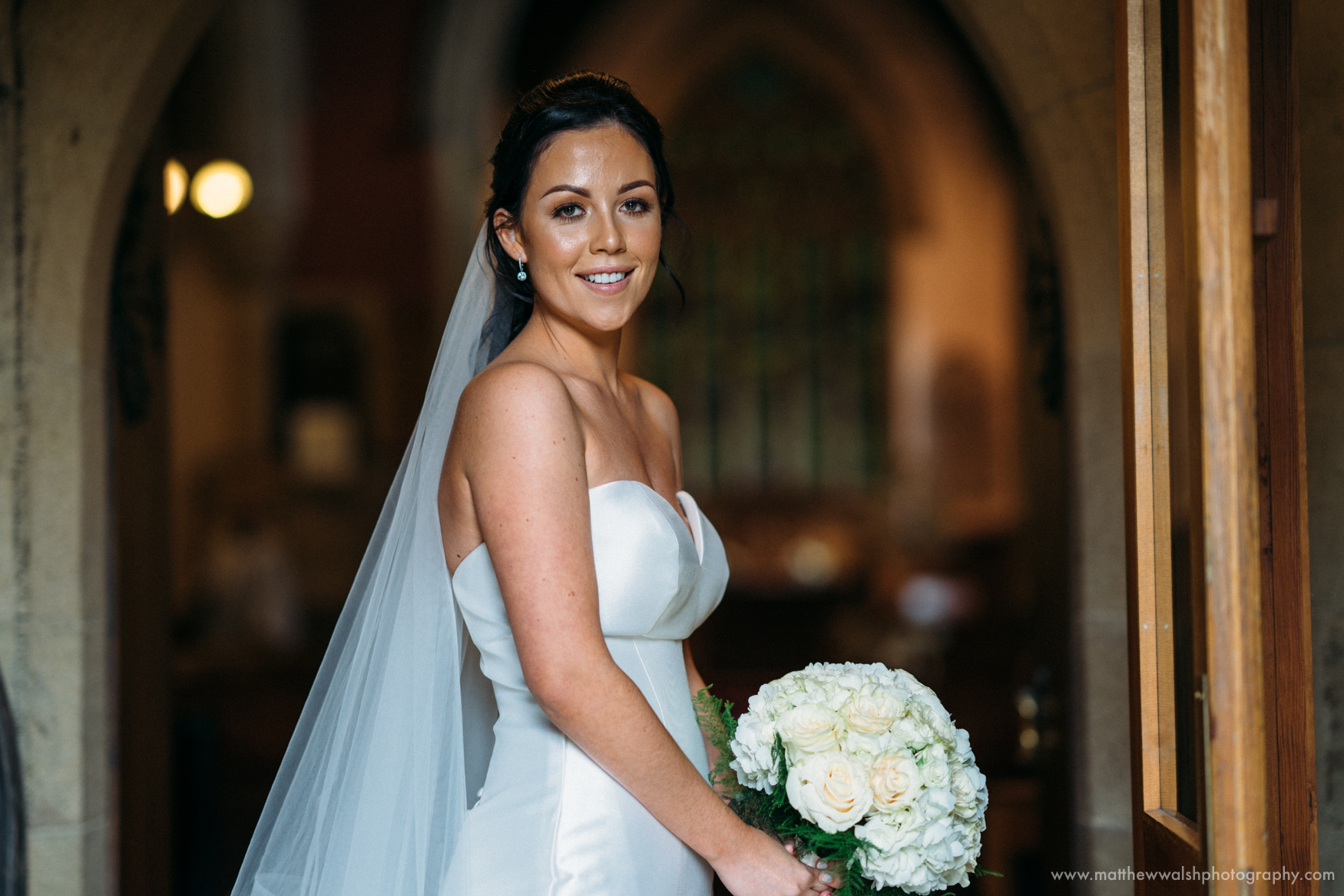 The bride poses for a quick photograph in the church doorway
