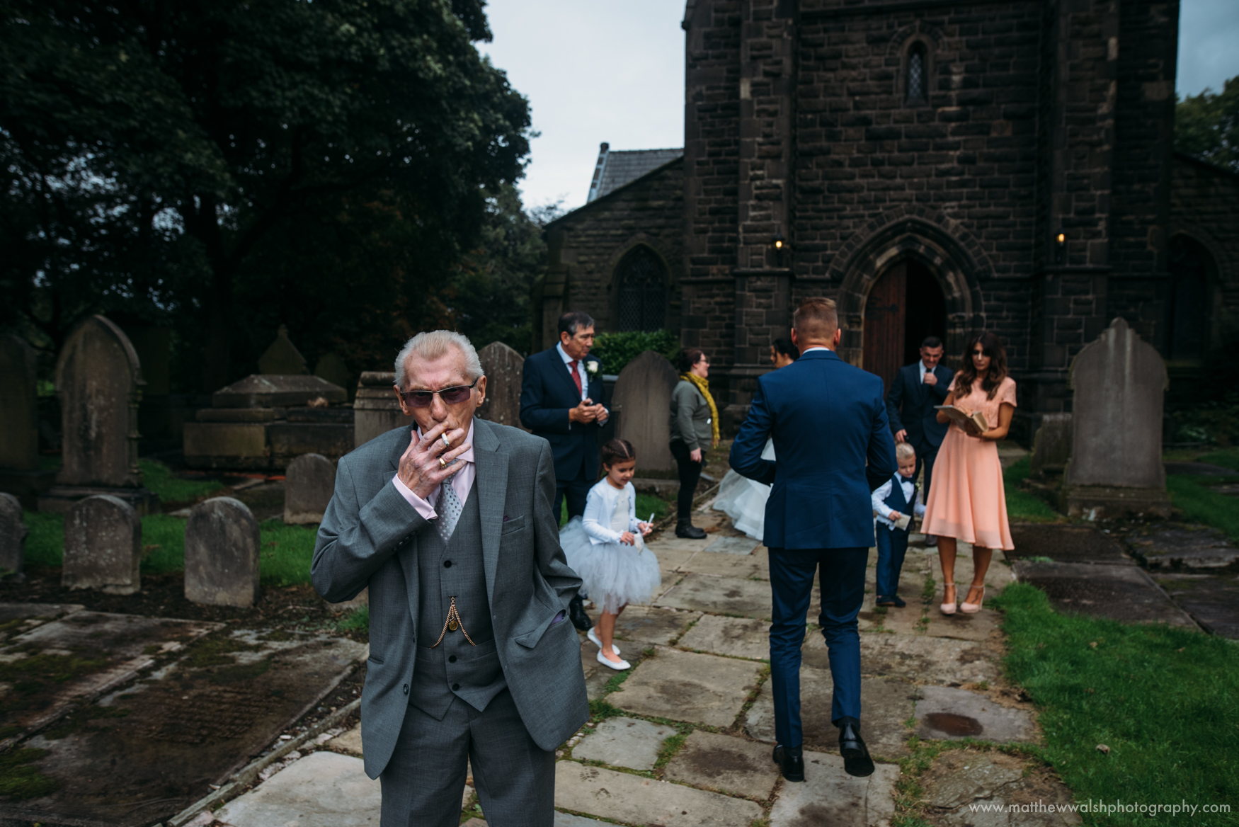 Grandfather of the groom has a quick cigarette after the ceremony