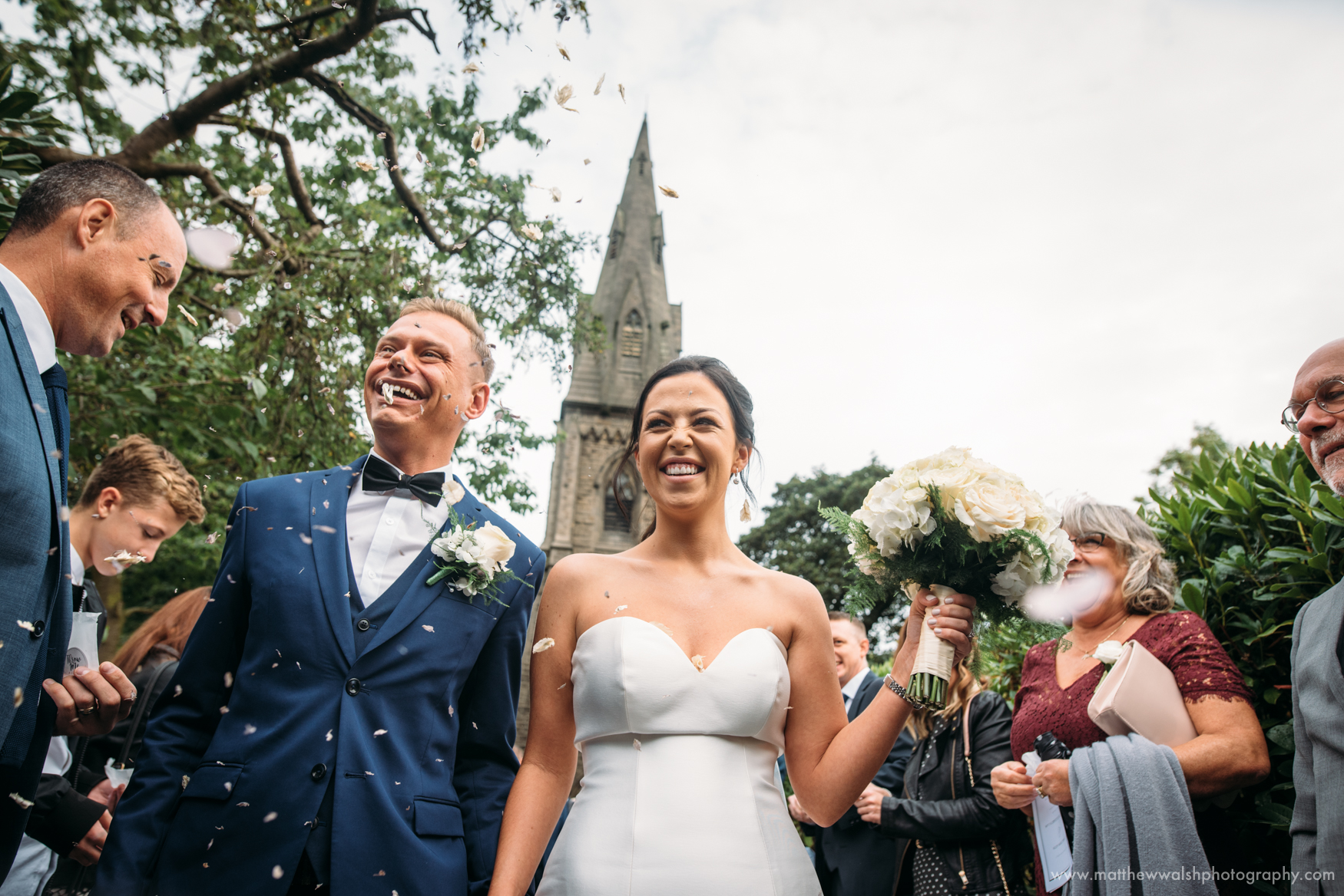 Recording the moment the newlyweds walk down an isle of confetti on leaving the church