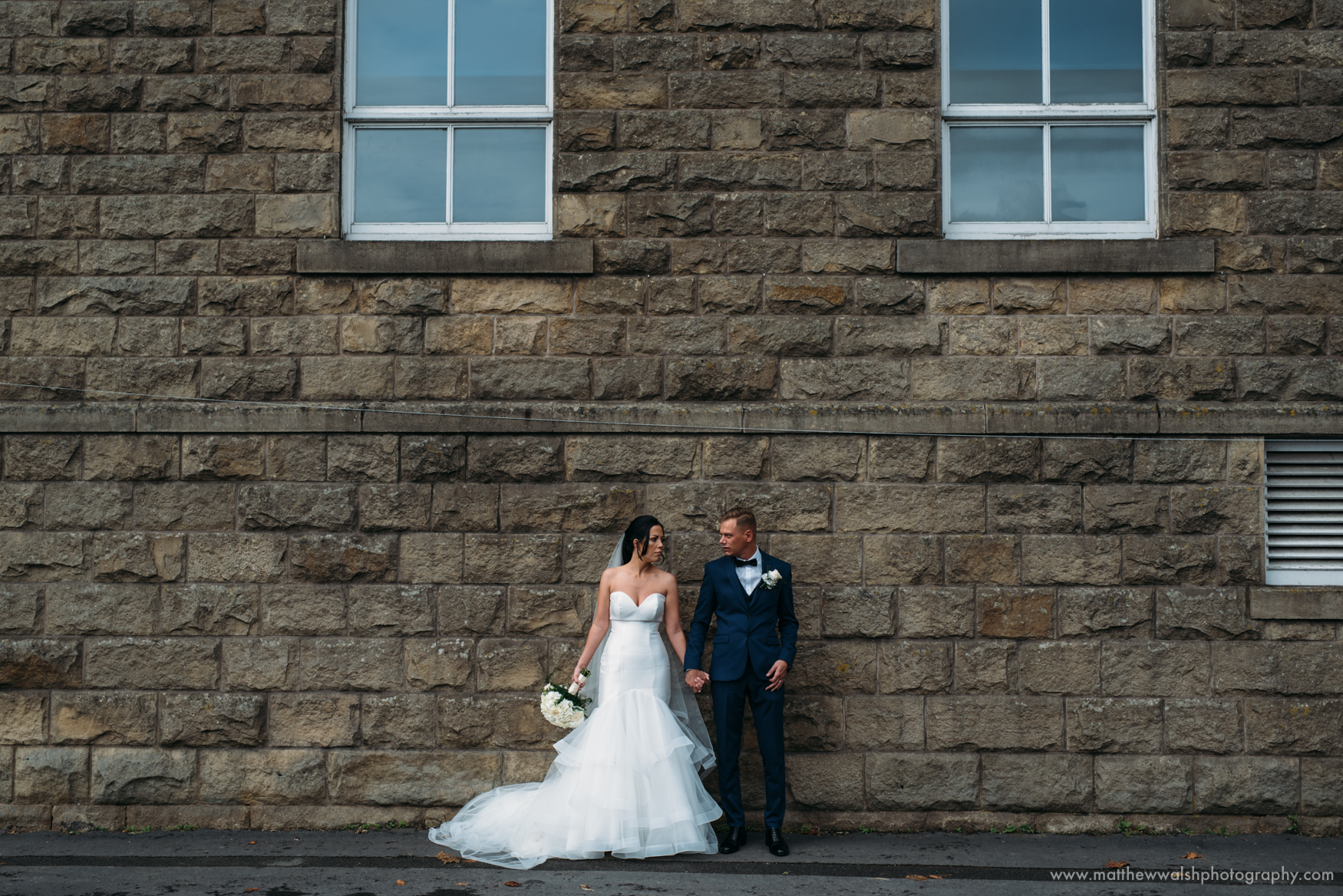 Bride and groom standing agains a wall for a distant posed photograph