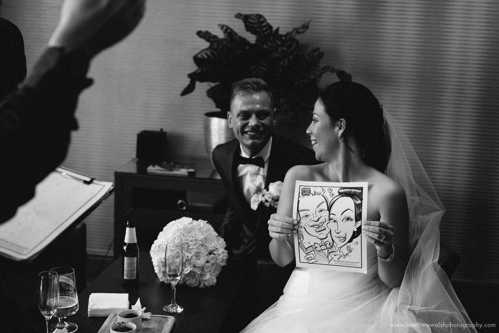 The bride and groom have their caricature done by the artist
