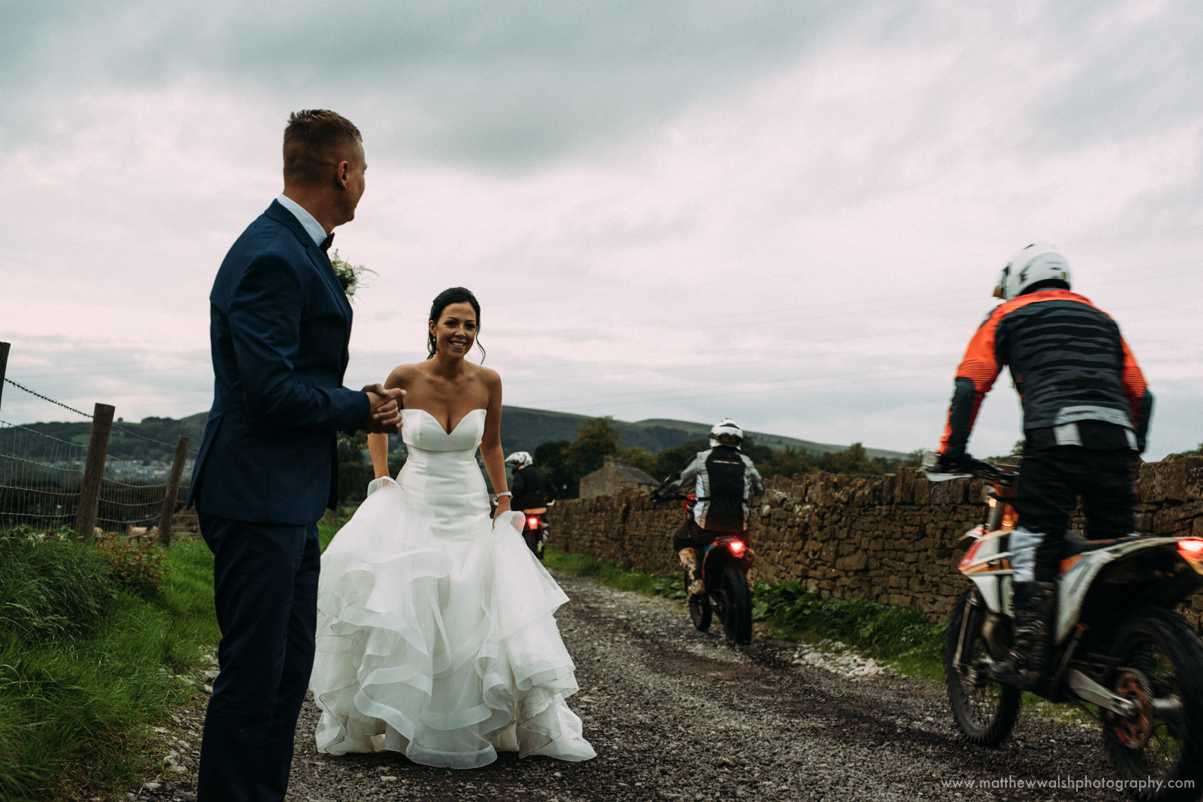 A natural reportage moment as motorbikes pass the bride and groom